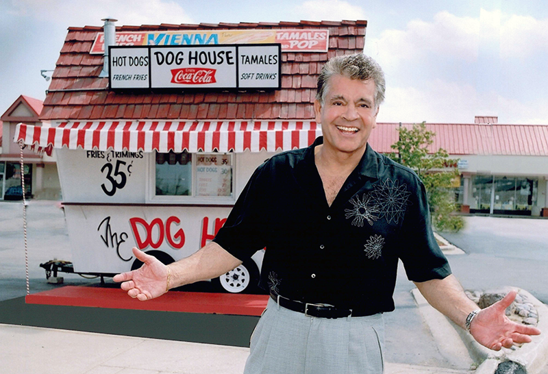 "Dick Portillo in front of a replica of the original Portillo's ""Dog House"""
